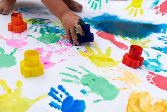 Handprint and footprint imprint by child in diffrent colors on white paper. Fun, education and sensory play. Stay at home with childen. Creativity and art.