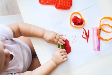 A small child at a table in a home interior sculpts from colored plasticine molds, rolling plastic with his hands. Home schooling.
