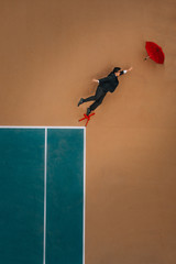 man in a suit reaching for a red umbrella flying away while standing on a red chair on a tennis court