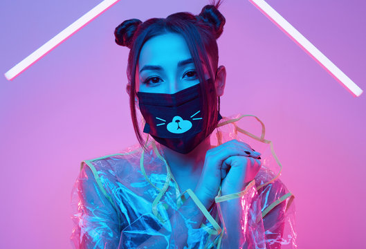 Virus mask Asian woman wearing face protection around colourful neon