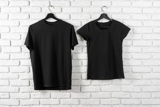 Black t-shirt hanging on a hanger against brick wall, front view