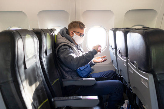 Guy in airplane, young man in glasses, medical protective sterile mask on his face sitting on plane using, apply anitizer for disinfect hands against coronavirus, virus bacteria. Pandemic covid-19