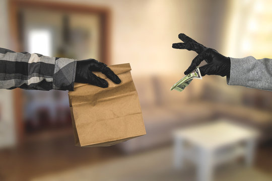 courier's hand in latex gloves holds a paper mock  up bag with food and female hand in latex gloves gives him