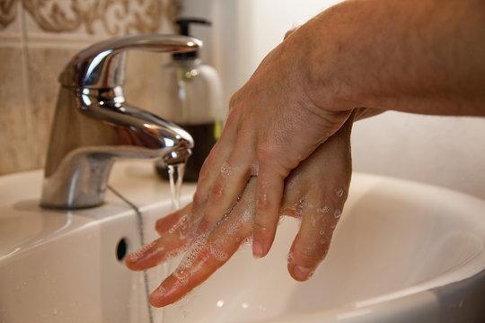 Hombre lavándose las manos con agua y jabón desinfectante