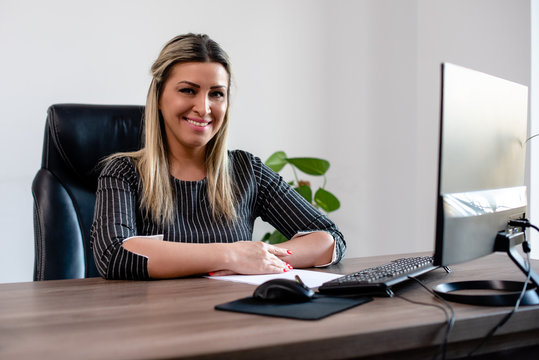 Business woman in office looking at camera