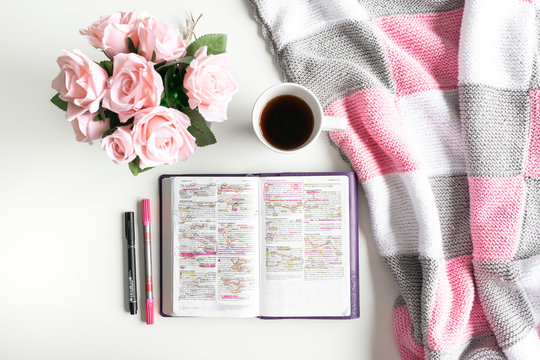 Pink Bible flat lay: Bouquet of pink roses, open Bible, black tea, coffee, journal, notebook, pen and pink blankets. Morning devotional. Rose, white, grey tones. Baselland, Switzerland - 02.04.2020