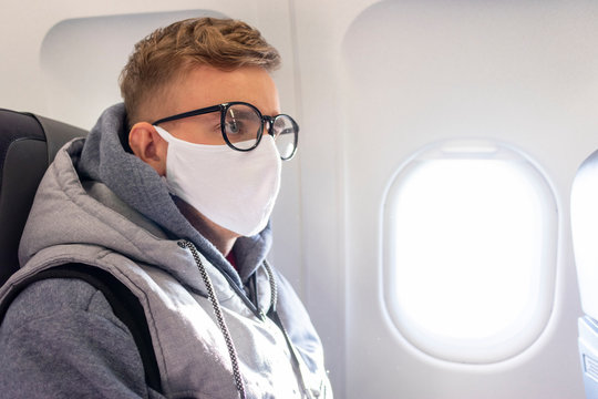 Serious guy, young man on airplane in glasses and medical protective sterile mask on his face sitting on plane, traveling. Coronavirus, virus concept. Pandemic covid-19. Evacuation of tourists