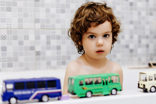 Little autistic boy in the bathroom playing with toy bus