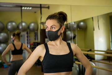 Young female athlete woman put on black designer protective mask sitting in empty gym. We are...