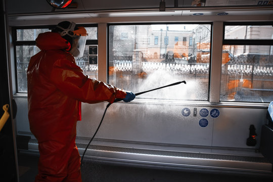 Municipality worker making the disinfection sparaying liquid sanitizer in public transport (bus) during Covid-19 outbreak - Vilnius, Lithuania, Europe