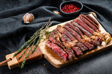 Tuinposter Steakhouse Grilled rib eye, ribeye steak on a chopping Board, medium rare. marbled meat. black background. top view