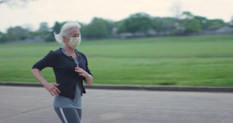 Aluminium Prints Jogging A mature woman wears a mask while out for a jog in response to fears of the coronavirus.