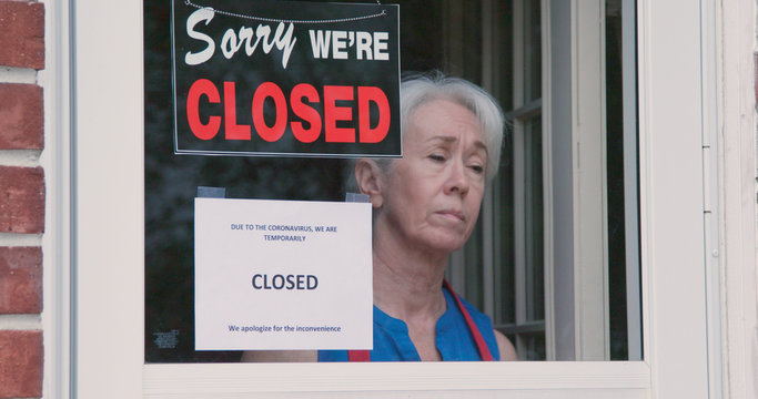 A worried mature small business owner turns the sign on her storefront from open to closed as a result of the shutdown issued because of the coronavirus.