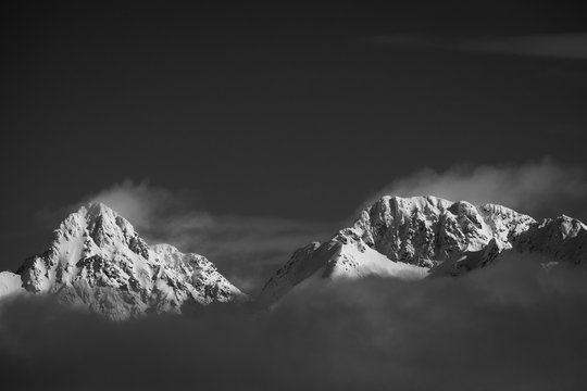 peaks of norway in black and white. peaks near to svolvaer town in lofoten islands during winter. snowy mountains shows their peaks partly hidden by clouds