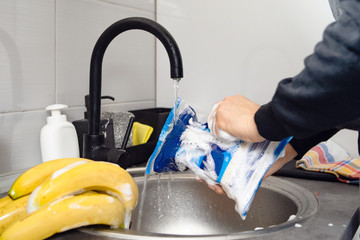 Side view on hands of unknown caucasian man person holding a rice bag under sink tap washing food with soap cleaning disinfection in water to disinfect from viruses or pollution at home in kitchen