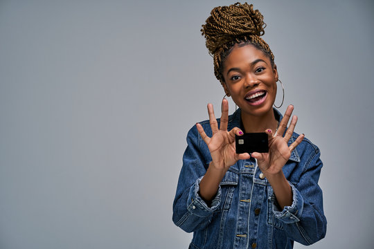 A girl with a smile in a jeans jacket shows a black bank credit card in her hands. Banking concept