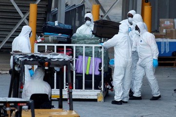 Workers handle luggage from the Zaandam of the Holland America Line cruise ship afflicted with coronavirus, at Port Everglades