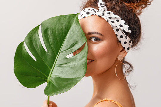 Beautiful African-American woman with tropical leaf on light background