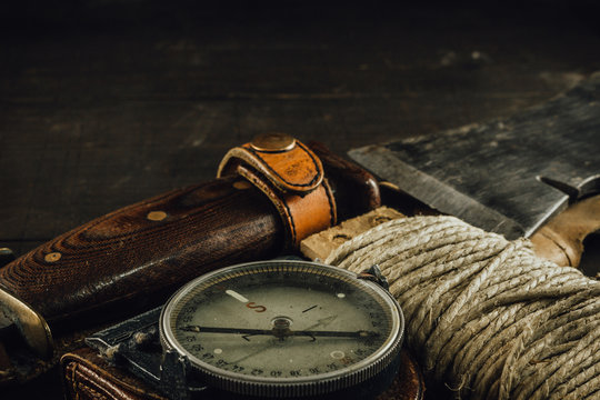 Old military compass, rusty hunting bushcraft knife, small axe and a linen rope on the dark wooden table. Leather cases, front view, survival hunting concept.