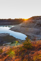 sunset over the sandy cliffs and lake landscape