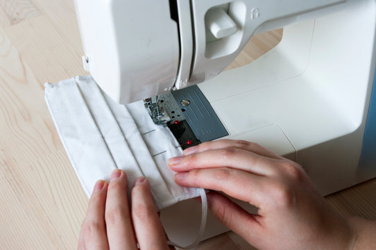 sewing mask at home. Female hands, making mask with Sew machine. Protect yourself against coronavirus