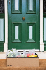 Close up of a home delivery box of fresh produce  sitting on a doormat during home isolation
