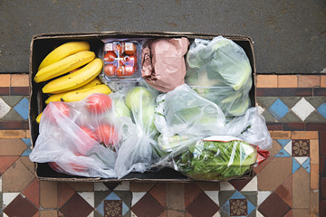 A box of fruit and vegetables is hand delivered and left on the doorstep
