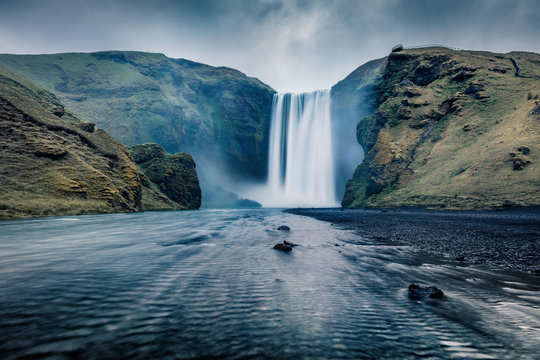 Dark night view of Skogafoss Waterfall. Fantastic summer landscape of Skoga river. Amazing outdoor scene of Iceland, Europe. Beauty of nature concept background.