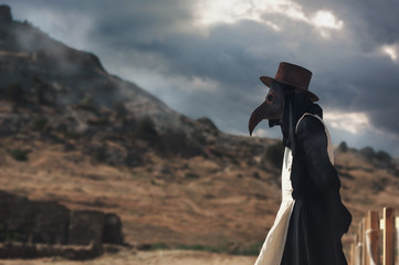 A man in historical masquerade costume of plague doctor in old gothic grange building of church. Epidemia protection costume. Pandemia horror mystical fantasy plague doctor