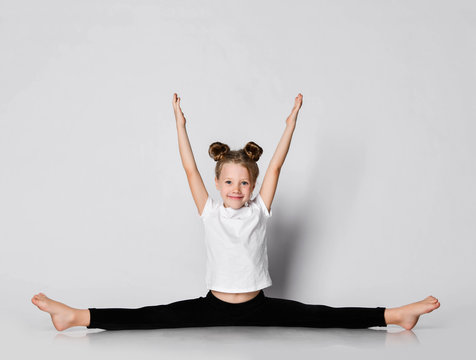 Smiling kid girl does gymnastic exercises at home splits with her hands up outstretched