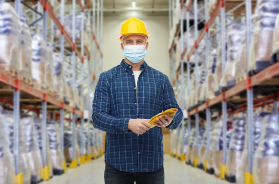 wholesale, logistic, people and export concept - male worker in safety helmet wearing face protective medical mask over warehouse background