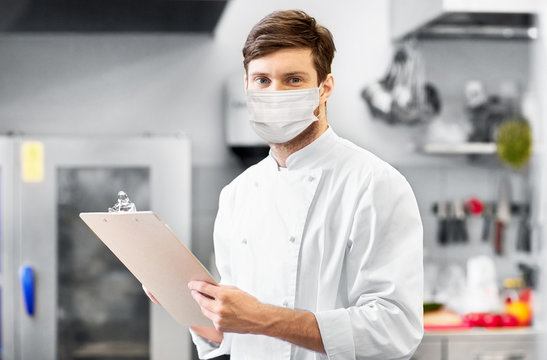cooking, profession and people concept - male chef cook with clipboard wearing face protective medical mask over restaurant kitchen background