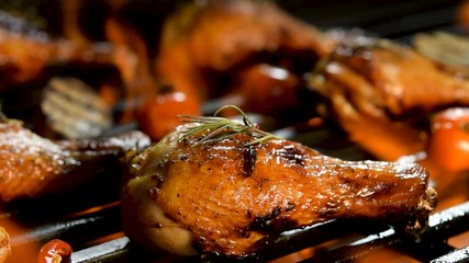 Fototapete - Close up grill roast bbq chicken leg with addition herbs and spices on the flaming grill .