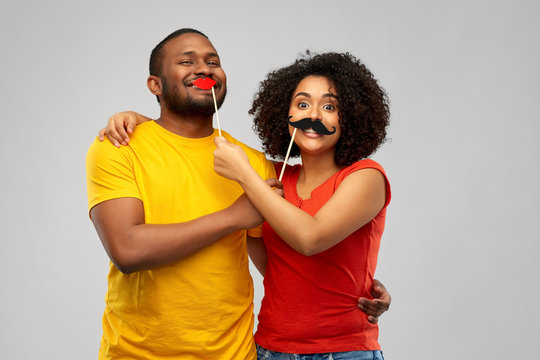 fun, photo booth and people concept - happy african american couple with party props hugging over grey background