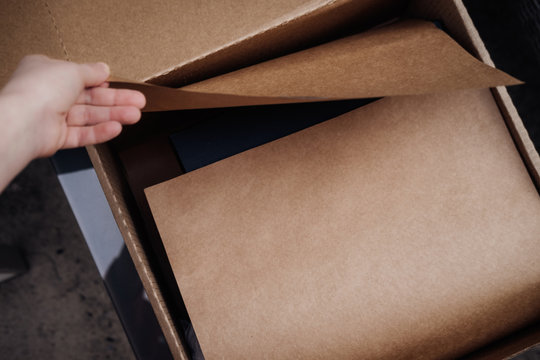 Woman's hand opening brown box with craft wrapping paper. Online shopping concept, copy space, from above