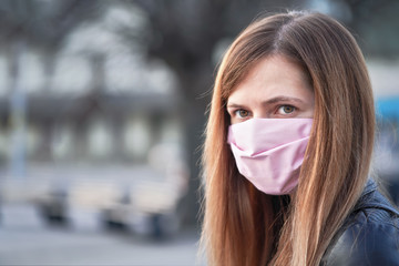 Young woman with hand made face nose mouth mask portrait, blurred empty city square behind her. Can be used during coronavirus covid-19 outbreak prevention Wall mural