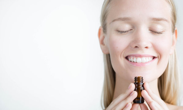 A pretty woman holding a bottle of essential oils, breathing the aroma. Natural alternative medicine.