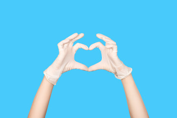 Hand gesture. Hand in a white latex glove showing Heart sign isolated on blue background.