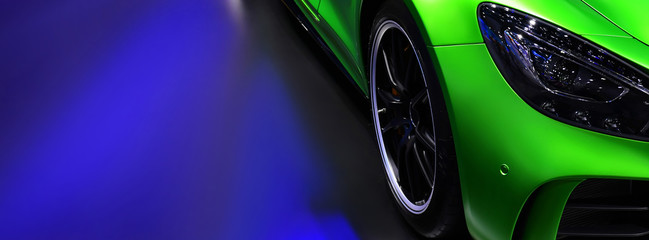 Wall Mural - Front headlights of green modern car on blue background