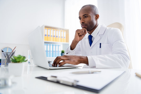 Photo of family doc dark skin guy watch modern technology notebook innovation medical cov viral news look screen online help wear white lab coat sitting chair table office clinic indoors