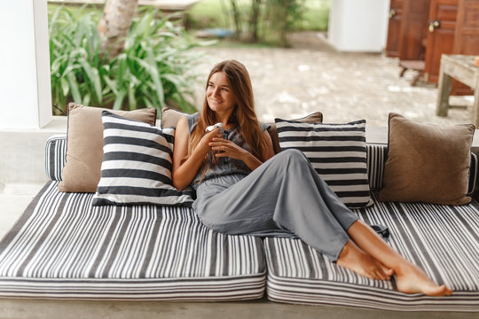 Home lifestyle woman relaxing enjoying luxury sofa patio furniture on outdoor patio living room. Happy lady lying down on comfortable pillows daydreaming thinking. Beautiful young caucasian girl