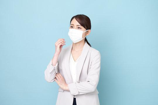 マスクをしながら腕を組んでいる女性