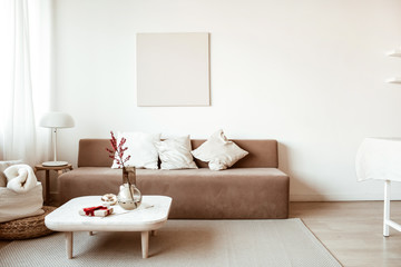 Modern interior design. Stylish bright living room decorated with comfortable sofa, coffee table, flowers, painting, white walls. Minimalistic apartment for rent. Wall mural