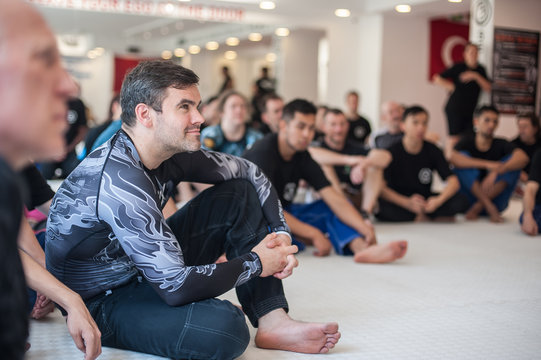 Group of student on martial arts seminar sits in dojo