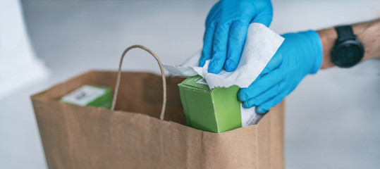 Spoed Fotobehang Wanddecoratie met eigen foto Coronavirus wiping down grocery packages after receiving home delivery wearing gloves, using disinfecting sanitizing wipes to wipe the surfaces clean. Cleaning of COVID-19 virus.