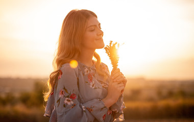 Happy woman with flowers enjoying sunset in field