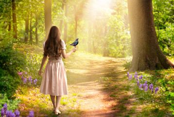 Lady girl with long hair in dress with bird in hand walking in fantasy enchanted fairy tale spring forest with blooming flowers and sun rays, mysterious road goes through trees in magical elvish wood