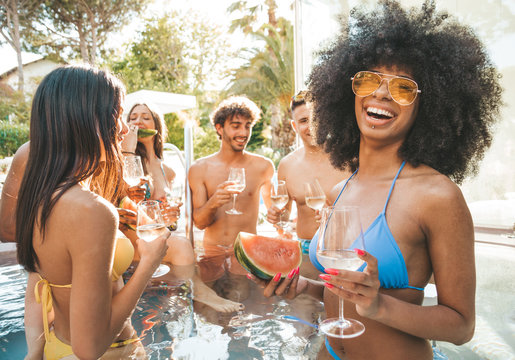 Portrait of group of young people having fun at pool party drinking champagne wine. Resort exclusive holiday concept