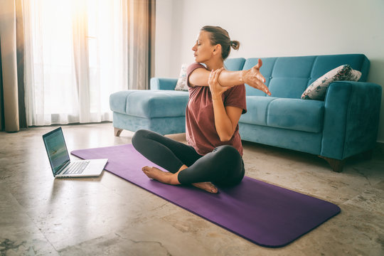 Attractive young woman doing yoga stretching yoga online at home. Self-isolation is beneficial, entertainment and education on the Internet. Healthy lifestyle concept