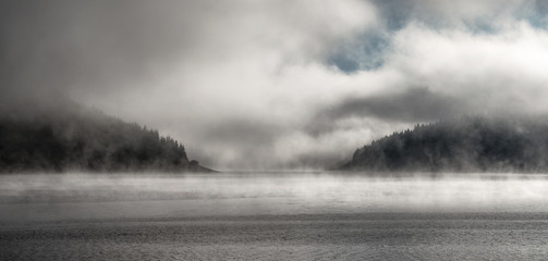 Morning fog over forest and mountain lake - 335284949